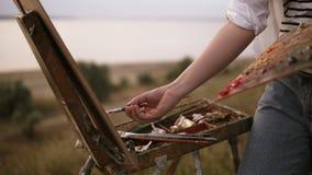 El artista de la muchacha en camisa rayada mezcla los colores en la paleta y los aplica a la lona en el caballete outdoors almacen de video
