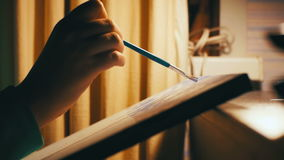 El artista de la mujer que se sienta en una tabla dibuja una imagen en casa metrajes