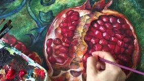 El artista de la pintura de la granada pinta una imagen con un cepillo, pinturas acrílicas metrajes