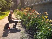 El artista de la señora pinta una imagen entre las flores en el parque Jardín botánico St Petersburg El verano de 2017 Imagen de archivo