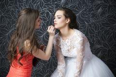 El artista de maquillaje aplica a la novia del lápiz labial Imagen de archivo libre de regalías