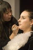 El artista de maquillaje aplica la sombra de ojo foto de archivo