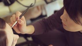 El artista de maquillaje aplica sombras de ojos en ojos del modelo almacen de metraje de vídeo