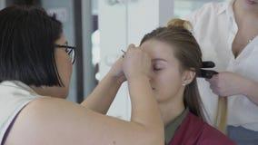 El artista de maquillaje Asian aplica maquillaje a la mujer que se hace a diseñar en el pelo metrajes