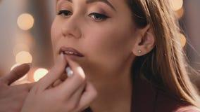 El artista de maquillaje cerca y dibuja la forma de los labios con un lápiz en la cara de un modelo rubio caucásico hermoso almacen de metraje de vídeo