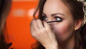 El artista de maquillaje compone las pestañas de la novia a la muchacha almacen de metraje de vídeo