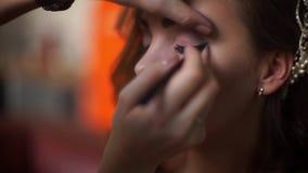 El artista de maquillaje compone los ojos de la novia a la muchacha almacen de metraje de vídeo