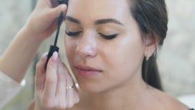 El artista de maquillaje del primer pinta las cejas de un cliente con un lápiz marrón Concepto para los salones de belleza, artis metrajes