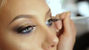 El artista de maquillaje del salón de la belleza dibuja el lápiz rubio del ojo del lápiz de ojos de las flechas metrajes