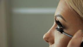 El artista de maquillaje del salón de la belleza induce las pestañas con un lápiz rubio del ojo del cepillo-rimel metrajes