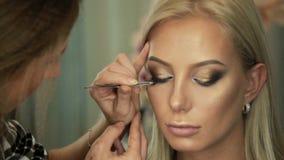 El artista de maquillaje del salón de la belleza pega las pestañas a los ojos rubios