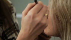 El artista de maquillaje del salón de la belleza pinta las sombras en los ojos con una mujer del Blonde del cepillo almacen de metraje de vídeo