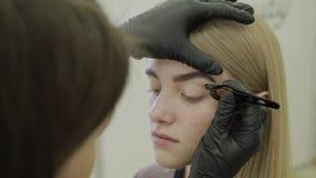 El artista de maquillaje despluma las cejas de una chica joven en un salón de belleza almacen de metraje de vídeo