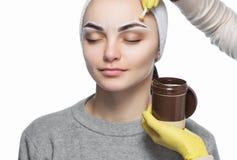 El artista de maquillaje despluma sus cejas, antes del procedimiento del maquillaje permanente imagen de archivo