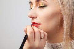 El artista de maquillaje en el estudio impone un maquillaje oriental lujoso a una chica joven rubia, en para cuya mano ella sosti foto de archivo libre de regalías