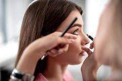 El artista de maquillaje está acentuando un párpado más bajo con lápiz de ojos negro imagenes de archivo