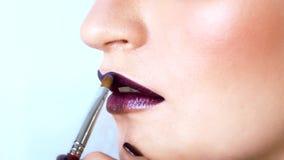 El artista de maquillaje está aplicando las mallas púrpuras brillantes en los labios del modelo con un cepillo Su boca está levem almacen de metraje de vídeo