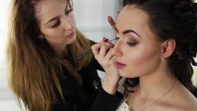 El artista de maquillaje está haciendo un maquillaje a la muchacha oscuro-cabelluda almacen de metraje de vídeo