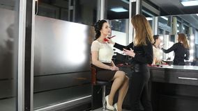 El artista de maquillaje está haciendo un maquillaje a la muchacha oscuro-cabelluda almacen de video