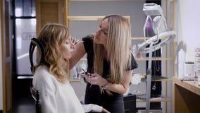 El artista de maquillaje está preparando el modelo para tirar, en el salón de belleza, aplicando sombras en sus párpados por el c almacen de metraje de vídeo