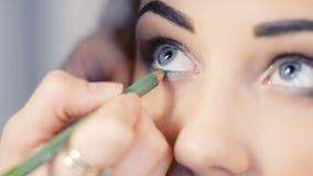 El artista de maquillaje hace maquillaje del ojo de los modelos metrajes