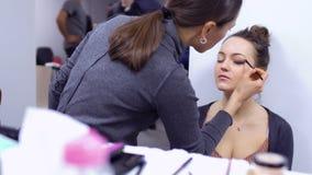 El artista de maquillaje hace hermoso para compensar a la actriz joven en teatro almacen de video
