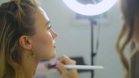 El artista de maquillaje hace maquillaje a la mujer almacen de metraje de vídeo