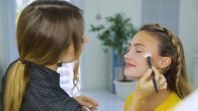 El artista de maquillaje hace maquillaje a la mujer metrajes