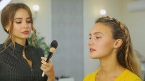 El artista de maquillaje hace maquillaje a la mujer almacen de video