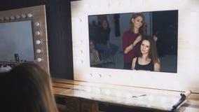 El artista de maquillaje hace que una muchacha el peinado hermoso refleja el espejo del maquillaje metrajes
