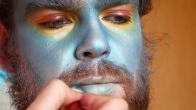 El artista de maquillaje hace un maquillaje de la etapa en el hombre Un avatar o un extranjero o un demonio del mar almacen de metraje de vídeo