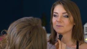 El artista de maquillaje hace una muchacha el maquillaje hermoso para la cara antes de un evento importante almacen de metraje de vídeo