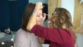 El artista de maquillaje hace una muchacha el maquillaje hermoso para las cejas antes de un evento importante almacen de video