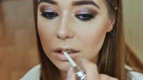 El artista de maquillaje de la muchacha pinta a la muchacha que los labios del ` s modelan en color rosado apacible almacen de video