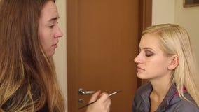 El artista de maquillaje de la mujer hace maquillaje a una chica joven almacen de video
