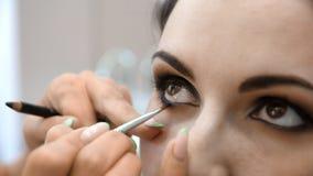 El artista de maquillaje de las manos aplic? maquillaje en la cara de una mujer joven Muchacha que hace maquillaje del ojo en un  almacen de video