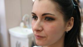 El artista de maquillaje de las manos aplic? maquillaje en la cara de una mujer joven Muchacha que hace maquillaje del ojo en un  metrajes