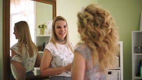 El artista de maquillaje mira a la novia y disfruta del trabajo hecho almacen de metraje de vídeo