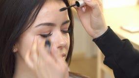 El artista de maquillaje pinta las cejas del modelo en el estudio almacen de video