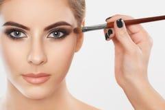 El artista de maquillaje pinta las cejas y los ojos a una muchacha hermosa foto de archivo
