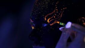 El artista de maquillaje pinta los ojos del polvo fluorescente de la muchacha bajo luz ultravioleta almacen de metraje de vídeo