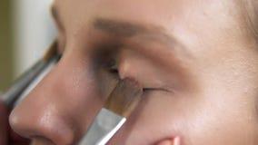 El artista de maquillaje pone el sombreador de ojos brillante ligero en los párpados del ` un s del modelo usando dos cepillos pr metrajes