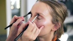 El artista de maquillaje profesional compensa el modelo lindo joven El poner del artista sombras de ojos usando dos cepillos almacen de video