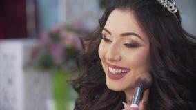 El artista de maquillaje profesional desconocido está aplicando maquillaje en la cara de la novia morena de risa encantadora con  metrajes