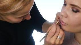 El artista de maquillaje profesional está aplicando el lápiz labial para el modelo joven atractivo Cámara lenta almacen de metraje de vídeo