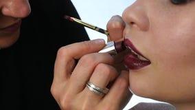 El artista de maquillaje profesional está aplicando el lápiz labial para el modelo joven atractivo Cámara lenta metrajes