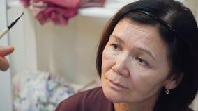 El artista de maquillaje profesional está haciendo el maquillaje para la mujer morena mayor metrajes
