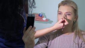 El artista de maquillaje profesional hace hermoso para compensar a la actriz en teatro almacen de metraje de vídeo