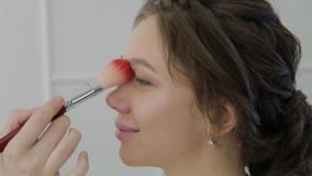 El artista de maquillaje profesional hace maquillaje a una mujer muy hermosa almacen de video