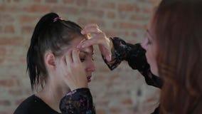 El artista de maquillaje profesional de la mujer del primer aplica la cera en cara de la muchacha linda joven para el maquillaje  metrajes